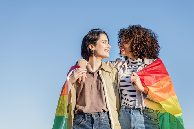 Lesbian couple wrapped in rainbow Pride Flag