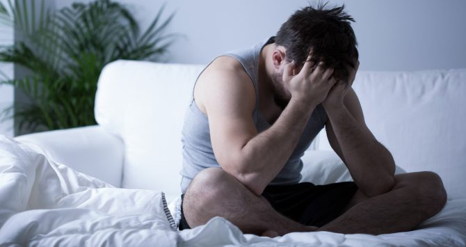 A depressed looking man holds his head in his hands