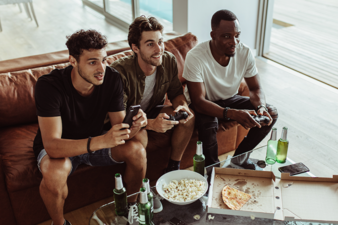 Guys playing video games on a couch