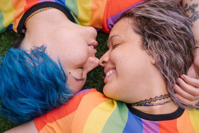 Lesbian teen couple wearing rainbow shirts