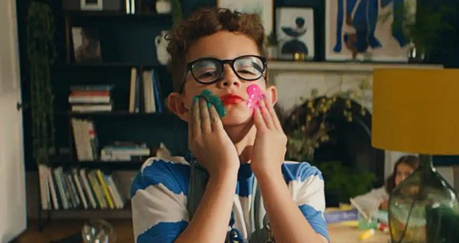 A young boy smears paint on his face in the John Lewis insurance advert